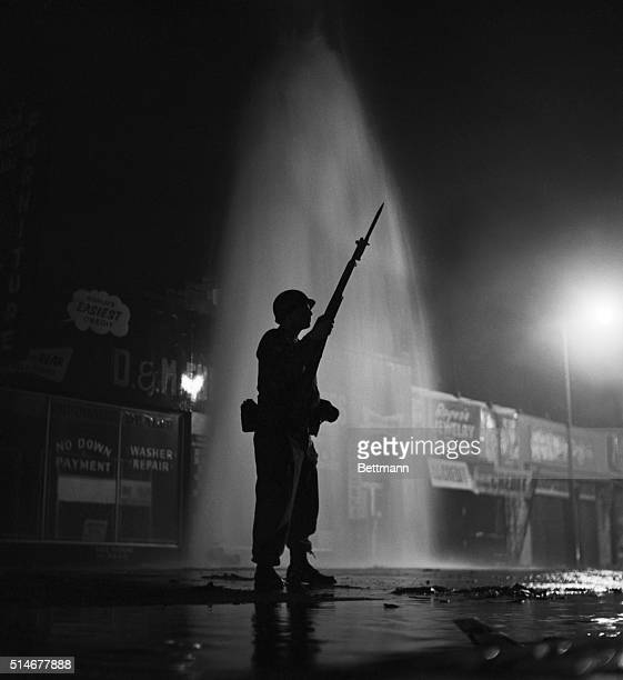 Los Angeles, CA: Silhouetted by the cool gush of a broken fire hydrant, a National Guardsman stands ready for further trouble in the strife-torn...