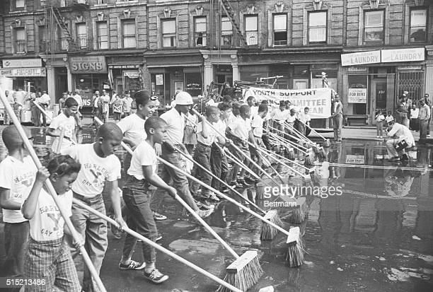 New York, NY- Negro youths form broom and bucket brigade, as they scrub streets, sidewalks, curbs and stoops in Harlem. The children were recruited...