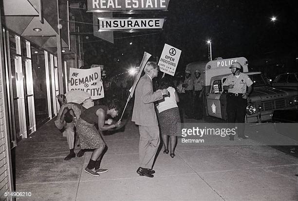 8/19/1966Chicago IL Civil rights demonstrators duck in an effort to avoid flying rocks and firecrackers hurled at them during a protest march against...