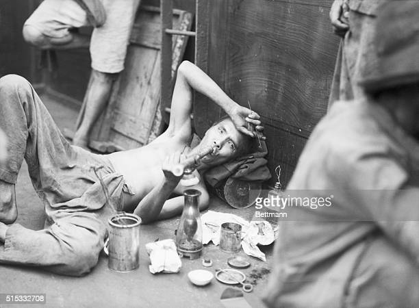 8/1943Aboard opium boat off Hong Kong The addict is all set to enjoy his pipe dream Beside him is the entire layout can of peanut oil lamp wire for...