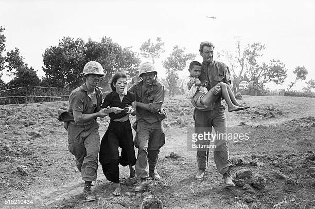 8/20/1965Chu Lai South Vietnam United States Marines help a wounded Vietnamese woman and her son to an evacuation helicopter after their village was...