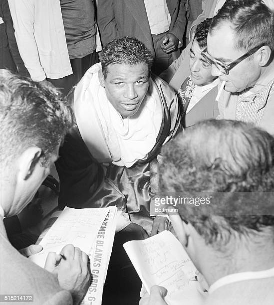 New York, NY- Sugar Ray Robinson talks to members of the press in his dressing room after he won the 10-round welterweight bout with Steve Belloise...