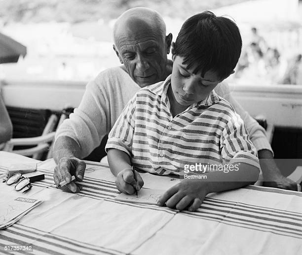 8/21/55La Garoupe France Famed Spanish painter and sculptor Pablo Picasso takes sometime give his young son Claude some instruction in the rudiments...