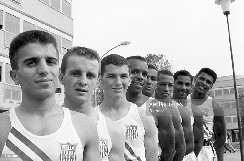 Rome, Italy- Members of the U.S. Olympic boxing team gather for a group photo. Pictured (L to R) are: Nicholas Spanakos, 22, featherweight; Jerry Armstrong, 24, bantamweight; Humberto Barrera, 18, flyweight; Edward Crook, 31, light middleweight; Quincy Daniels, 19, light welterweight; Harry Campbell, 22, light middleweight, and Cassius Clay, 18, light heavyweight.