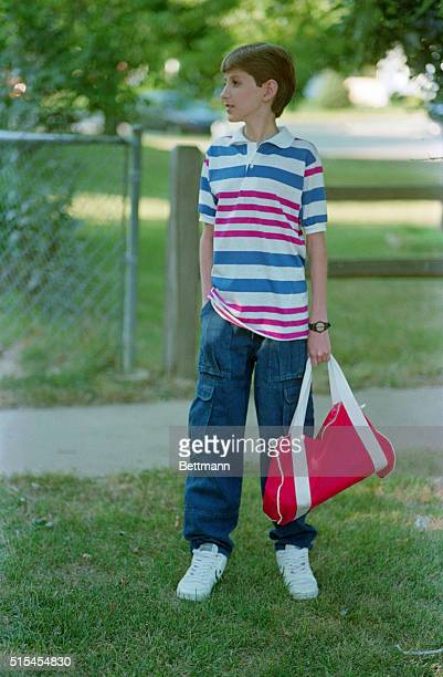 Ryan White holds his school bag as the waits for the bus near is home Ryan started his first day of classes in high school at Western Schools...