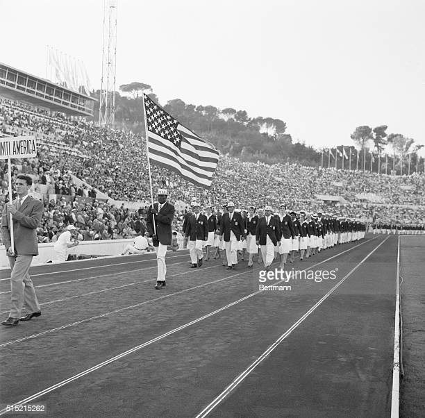 8/25/60Rome Italy American decathlon athlete Rafer Johnson of Kingsbury Calif carries the flag as the US Olympic contingent parades through Marble...