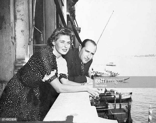 Venice, Italy: From a balcony of the Grand Hotel, Ingrid Bergman, movie star, and Roberto Rossellini, Italian director who she wed after divorcing...
