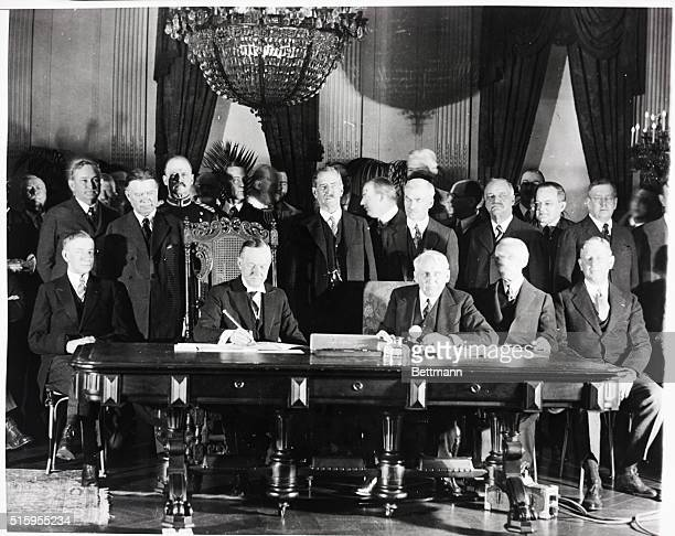 8/27/1928Washington DC President Calvin Coolidge signs the KelloggBriand Pact in his office Secretary of State Frank B Kellogg is seated to the left...