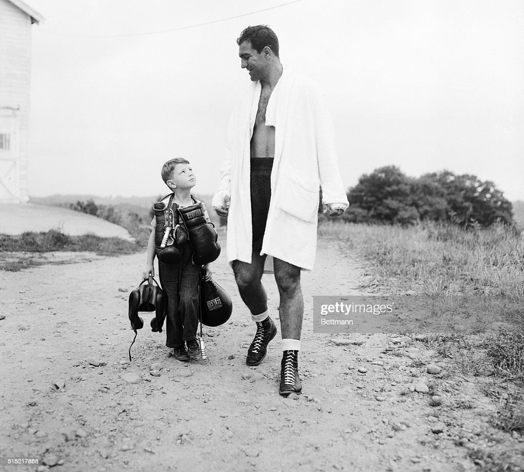 Rocky Marciano with Boy Carrying His Gear : News Photo