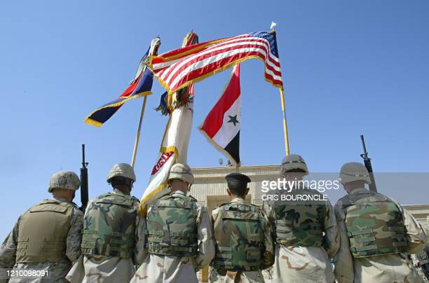 82nd Airborne Division troops, marines and an Iraqi soldier hold national and army flags during the ceremony of transfer of authority from the 82nd...