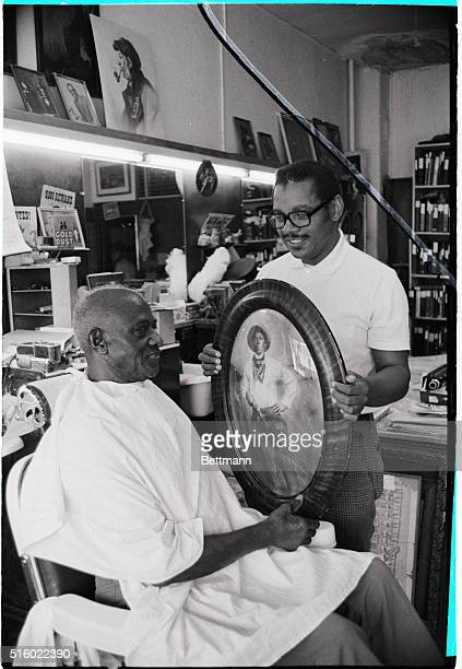 Paul Stewart shows a photograph of an oldtime black cowboy to customer Herbert Robinson in his barber shop in Denver Stewart has been collecting...