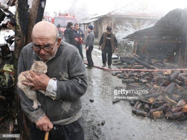 83yearold Ali Mese carries a cat saved from a fire by firefighters during snowfall as firefighters try to extinguish the fire broken out at old man's...