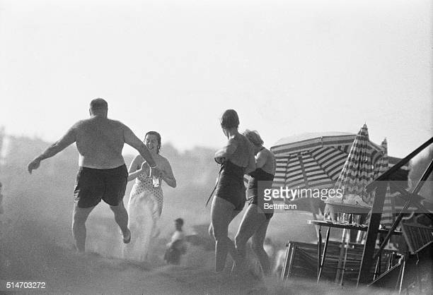 A playful Farouk throws sand with his foot at pretty playmates as the portly exking of Egypt enjoys the resort of Anzio a fashionable beach near Rome...