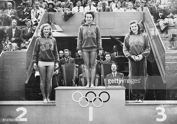 London, England: Vickie Draves of Los Angeles holds the place of honor on the winner's rostrum at empire pool after her victory in the Olympic...