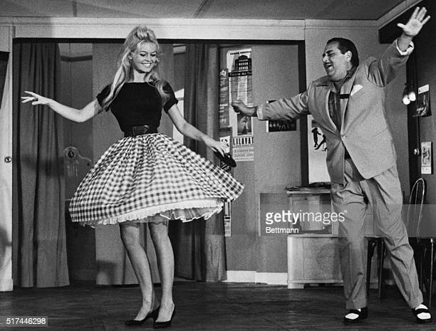 "Nice, France- Displaying a shapely set of gams, French ""sex-kitten"" Brigitte Bardot does the cha-cha under the direction of comic Darius Moreno...."