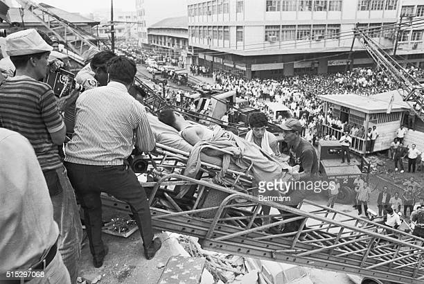 8/5/1968Manila Philippines As thousands watch in the background rescue teams remove survivors found in the rubble of the Ruby Towers apartment house...