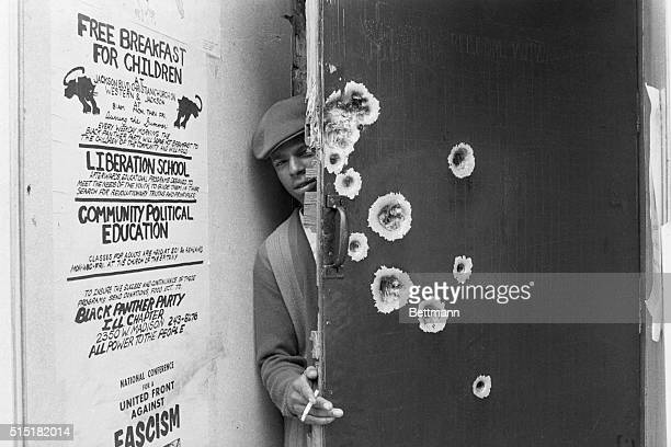 Chicago, IL- An unidentified member of the militant Black Panthers peeks around a bullet pocked door which police blasted with gunfire early July...
