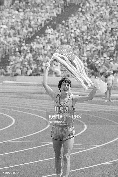 Los Angeles, CA- American runner Joan Benoit jogs around the Los Angeles Coliseum track carrying the American flag, after winning the gold medal in...