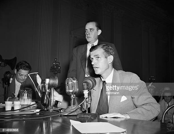 Alger Hiss on the stand holding photograph of Chambers which he was asked to identify by Robert Stripling chief investigator for the House UnAmerican...