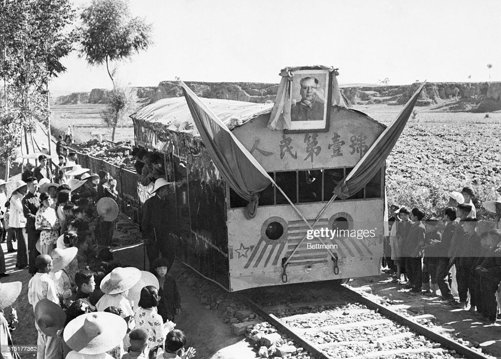 Banners and a portrait of Communist Party Chairman Mao Tse-Tung adorn the front of this strange-looking freight train making its first run Yuhsien County, Shansi Province, China. According to information supplied by the Chinese Communists, the 125-mile railroad was built by the people of the county to carry coke to the Yuhsien power equipment plant. The locomotive, powered by a converted automobile engine, pulls six cars, each loaded with three tons of coke. Photo and caption material are from a Chinese Communist source