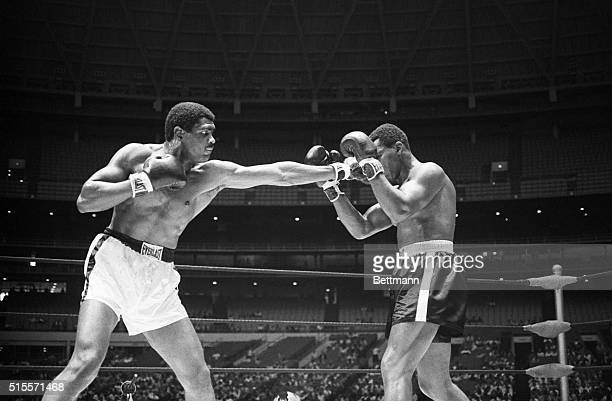 Houston, Texas: Chicago's Ernie Terrell's long left penetrates the peek-a-boo defense set up by Philadelphia's Thad Spencer in the World Boxing...