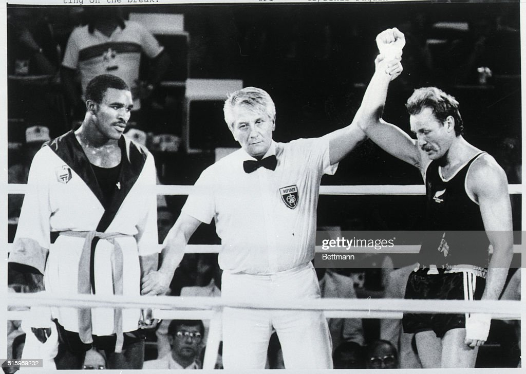 Los Angeles, CA- Yugoslavian referee Gligorije Novicic (C) raises the hand of New Zealand boxer Kevin Barry as dejected Evander Holyfileld (R) of Atlanta looks on. Holyfeild had earlier knocked Barry through the ropes, and had the fight well in hand until Novicic disqualified him at the end of the second round for hitting on the break.