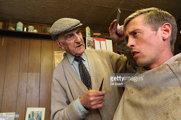 89yearold Aaron Biber cuts the hair of his favorite footballer Peter Crouch in his hairdressing salon which was damaged during the riots on Tottenham...