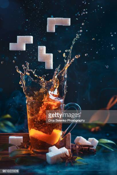 8-bit video game in real life concept with copy space. Splash of tea in glass latte cup with sugar Tetris pieces. Creative action food photography.