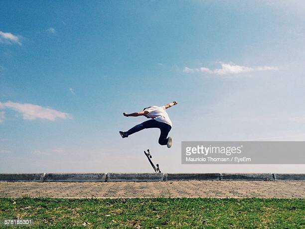 8Full Length Of Man Performing Stunt While Skateboarding Against Sky