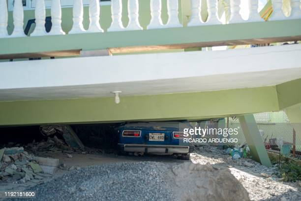 A car lies under a collapsed house damaged by a 58 earthquake seen in Guanica Puerto Rico on January 6 2020 A 58magnitude earthquake shook Puerto...