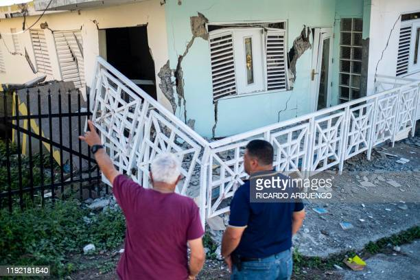 Two men stand in front of a house collapsed by a 58 earthquake in Guanica Puerto Rico on January 6 2020 A 58magnitude earthquake shook Puerto Rico on...