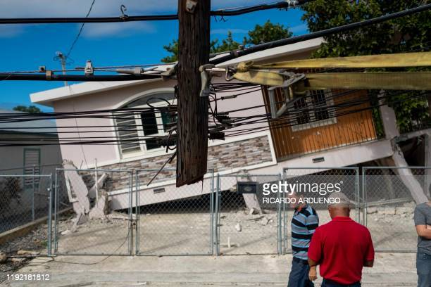 TOPSHOT People pass by a house damaged by a 58 earthquake in Guanica Puerto Rico on January 6 2020 A 58magnitude earthquake shook Puerto Rico on...