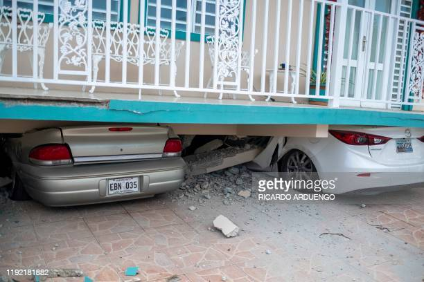 Cars are seen under a collapsed house damaged by a 58 earthquake in Guanica Puerto Rico on January 6 2020 A 58magnitude earthquake shook Puerto Rico...