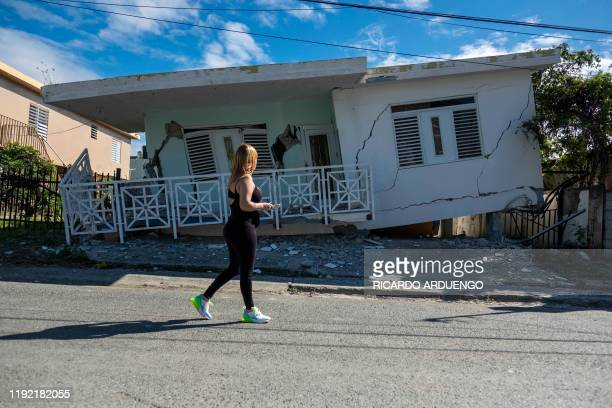TOPSHOT A woman passes by a house damaged by a 58 earthquake in Guanica Puerto Rico on January 6 2020 A 58magnitude earthquake shook Puerto Rico on...