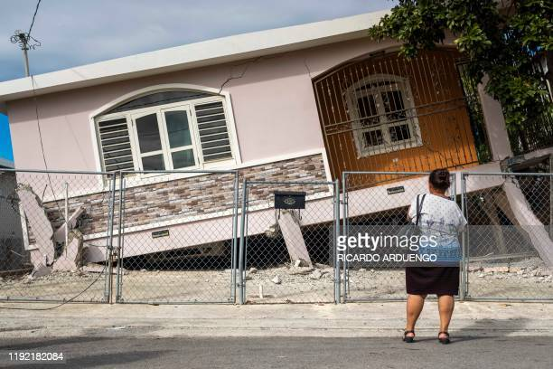 A woman stands in front of a house damaged by a 58 earthquake in Guanica Puerto Rico on January 6 2020 A 58magnitude earthquake shook Puerto Rico on...
