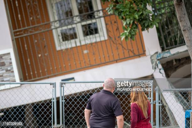 A couple stand in front of a house damaged by a 58 earthquake in Guanica Puerto Rico on January 6 2020 A 58magnitude earthquake shook Puerto Rico on...