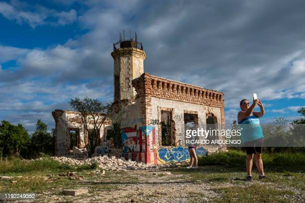 Tourists take pictures of the collapsed wall of the ruins of an iconic landmark lighthouse in Guanica Puerto Rico on January 6 after it was destroyed...