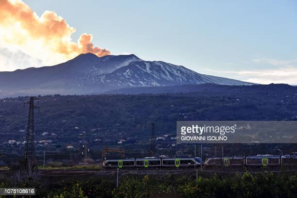 Smoke rises from Mount Etna as seen at sunset from the city of Giarre Catania on December 26 2018 as a passengers train passes A 48magnitude...