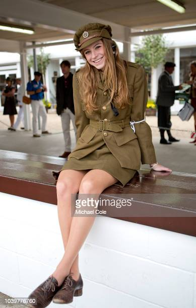 A young lady dressed in military uniform wearing an ATS cap badge sitting on the Pit Wall Lane at the 20th anniversary of the Goodwood Revival at...