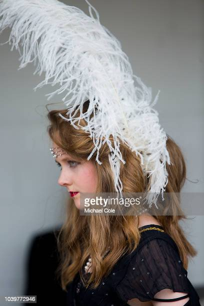 A young lady sporting an ostrich feather in her hair in the Pit Lane Area at the 20th anniversary of the Goodwood Revival at Goodwood on September...
