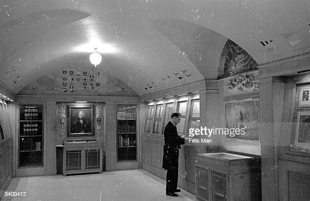 An employee of Lloyd's of London in the Nelson Room In the case underneath Horatio Nelson's portrait is the logbook of HMS Euryalus his signal...