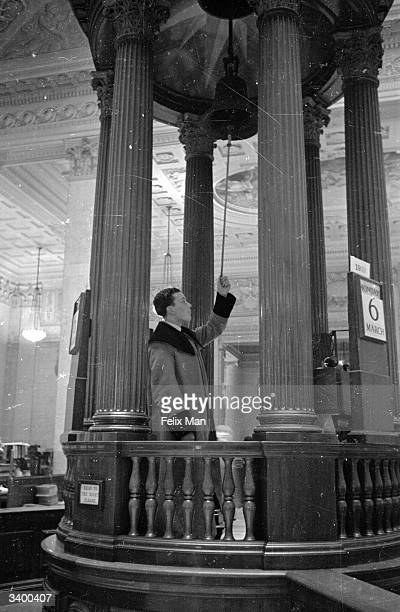 An employee sounding the bell of frigate Lutine which hangs in the Underwriters' Room at Lloyd's of London headquarters of marine insurance It is...