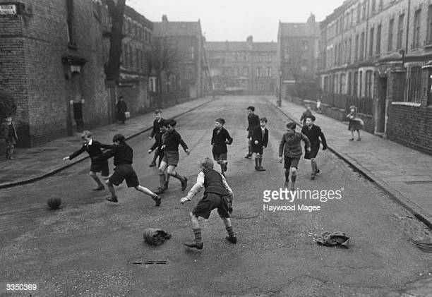 Boys playing football in a residential street in London Original Publication Picture Post 5005 Children's Street Games pub 1950