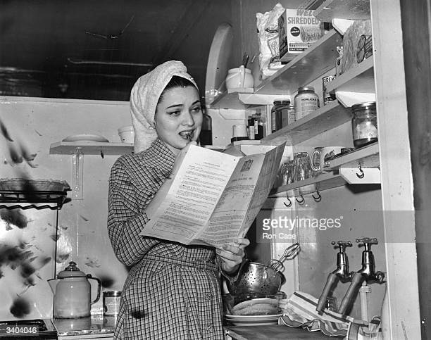 Julie Wilson star of the show 'Kiss Me Kate' finds time to fill in her census form as she potters about her kitchen