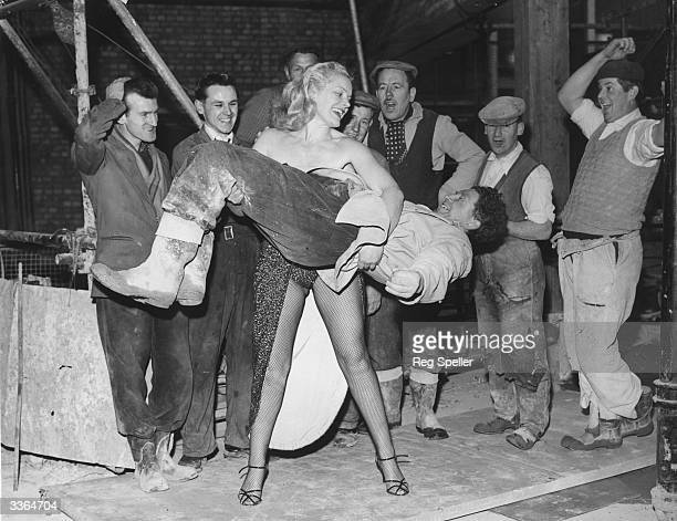 Men working on the site of Quaglino's new banqueting rooms look on in amazement as strongwoman Joan Rhodes demonstrates her strength by lifts one of...