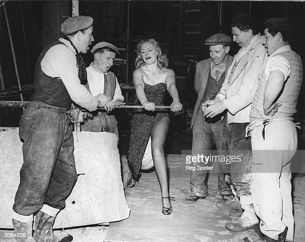 Men working on the site of Quaglino's new banqueting rooms look on in amazement as strongwoman Joan Rhodes demonstrates her strength by bending an...