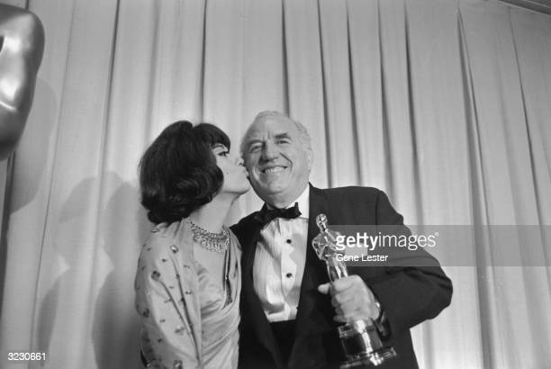 American actor Ed Begley smiles and holds his Best Supporting Actor Oscar as American actor Rita Moreno kisses him backstage at the Academy Awards,...