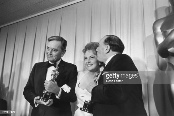 British director Sir David Lean and American actress Olivia de Havilland smile as producer Sam Spiegel kisses De Havilland at the Academy Awards,...