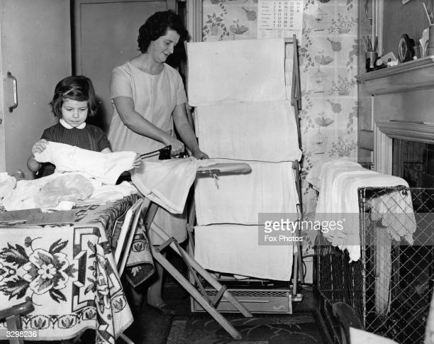 Mrs June Fowler a mother of triplets at the ironing whilst her elder daughter Susan helps her fold clothes
