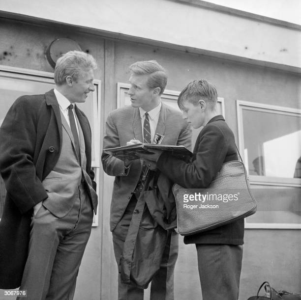 Scottish footballers Billy McNeill and Denis Law signing autographs for a young fan after their arrival at Heathrow Airport for Scotlands game...